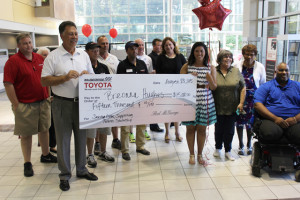 Breonna Hughes, with family and friends, accepts the Saving Lives, Supporting Futures Scholarship from representatives of McGeorge Toyota and Drive Smart Virginia.