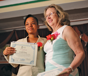 Nadene Brunk poses with a recent graduate who will serve as a skilled birth attendant in Haiti.